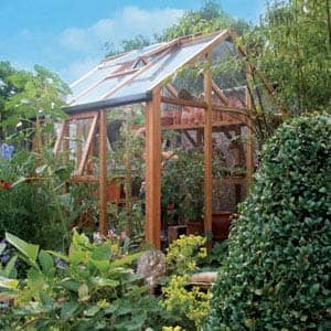 cedar greenhouse with trees surrounding it
