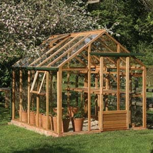 red cedar greenhouse in garden with trees